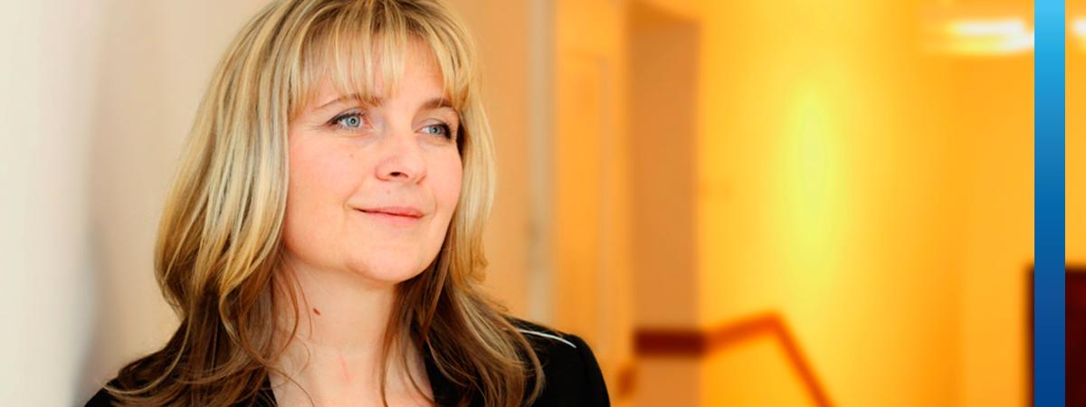 Porträt einer blonden Frau im schwarzen Blazer, die an Wand gelehnt steht