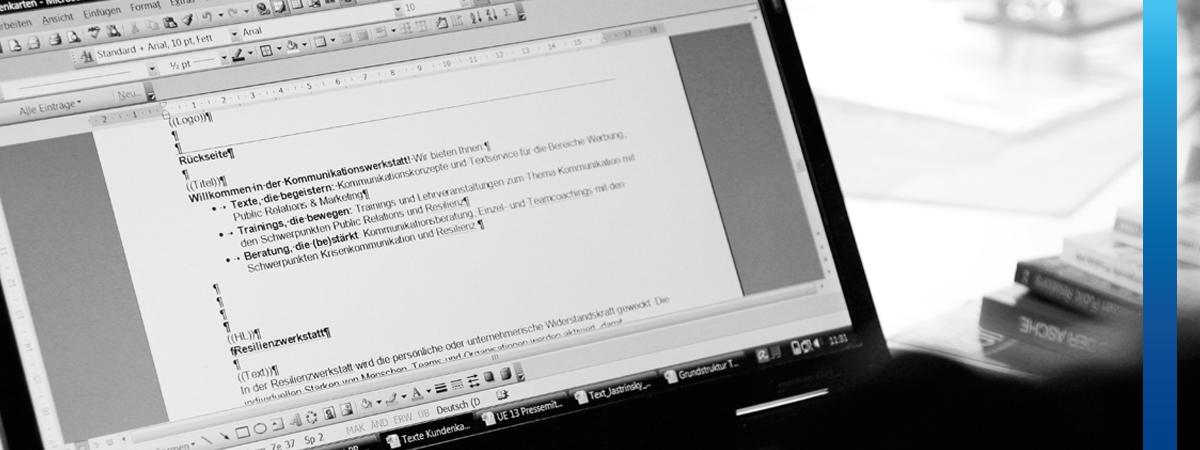 """Schwarz-weißes Bild, Blick auf Monitor von schwarzem Laptop, eine Textdatei ist geöffnet mit Text """"Willkommen in der Kommunikationswerkstatt"""""""