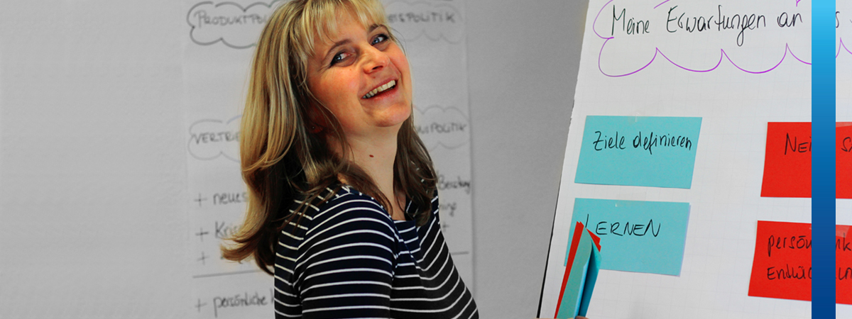 Lachende Frau mit bunten Moderationskarten steht vor Flipchart mit Text Ziele definieren, Lernen, Nein-Sagen und Persönlichkeitsentwicklung